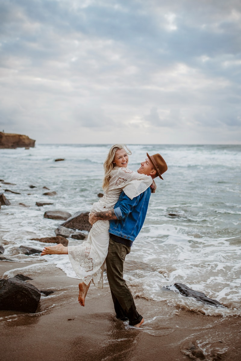 San Diego Couples Photography, man lifting woman up by the water