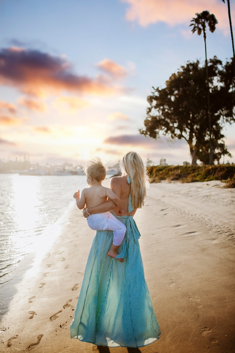 San Diego Family Photography, mother in teal dress, holding little boy and looking at the sunset