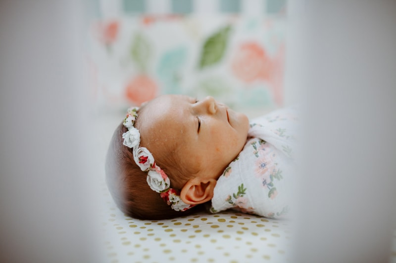 San Diego Newborn Photography, looking at baby through the slats of her crib