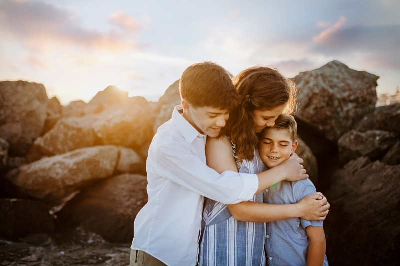 San Diego Family Photography, siblings hugging next to a rock pile on the beach