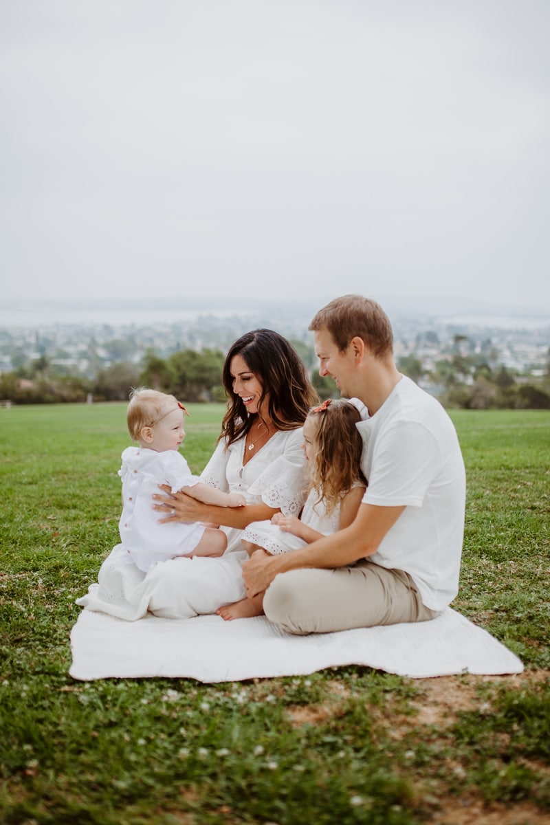 San Diego Family Photography, family of four in all white sitting on a blanket in the grass