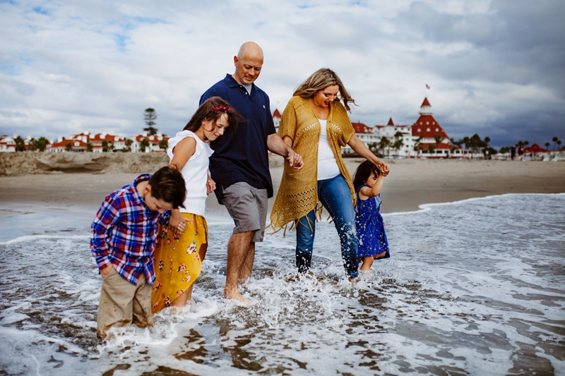 San Diego Family Photography, family of 5 walking slowly into the ocean
