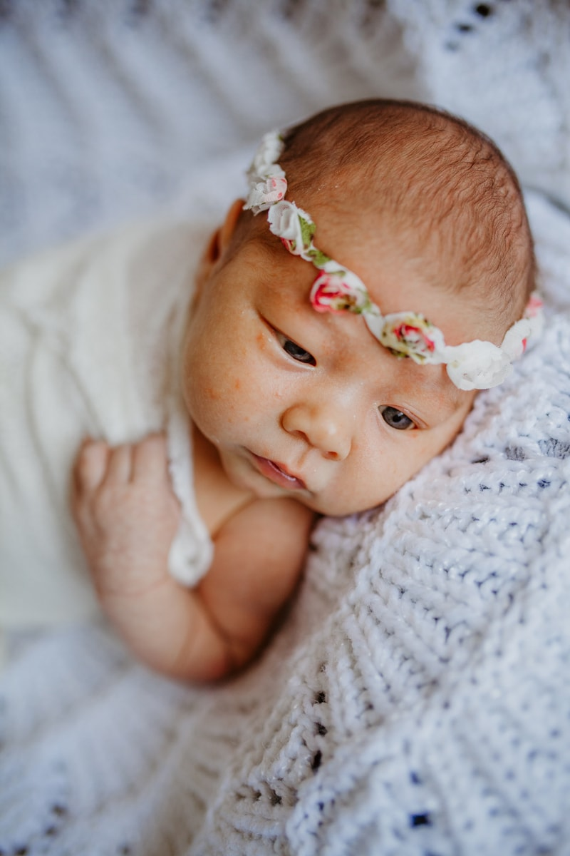 San Diego Newborn Photography, baby laying on white knit blanket with floral headband