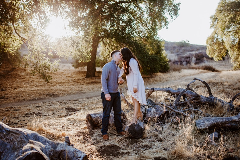 San Diego Couples Photography, woman standing on log kissing man