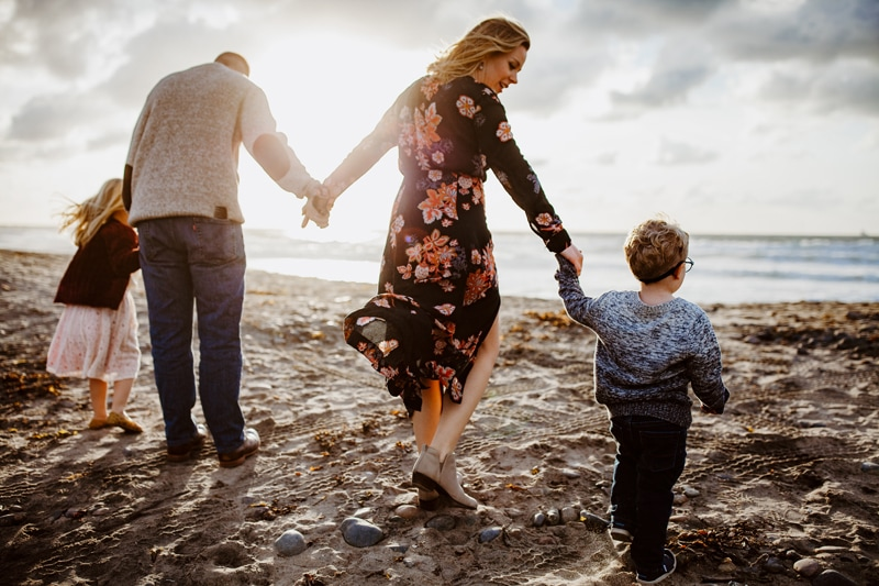 San Diego Family Photography, family of 4 walking toward the ocean with sunset in the bkg