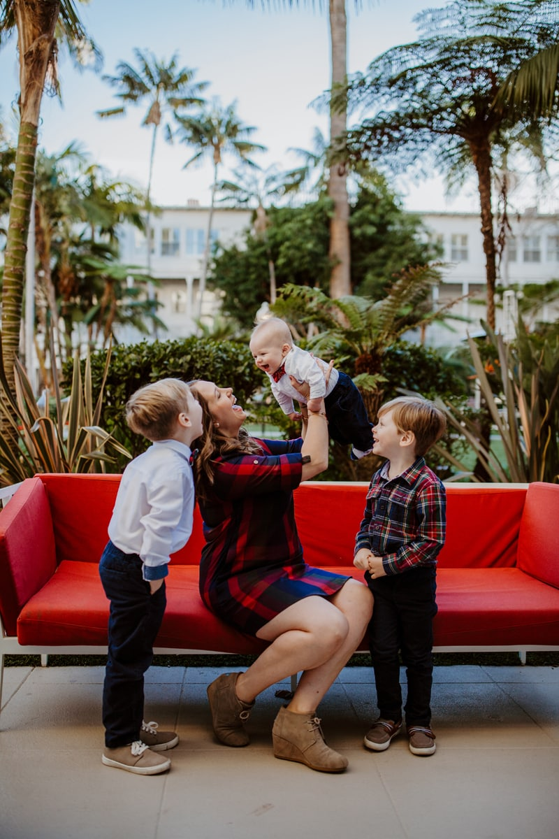 San Diego Family Photography, mother lifting up laughing baby into the air