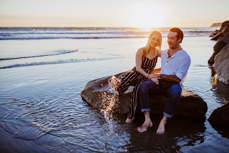 San Diego Couples Photography, couple sitting on a rock in the water with woman splashing with her foot