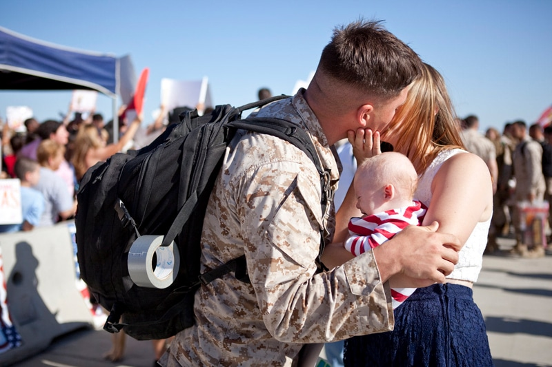 San Diego Military Homecoming, you couple kissing while holding their baby