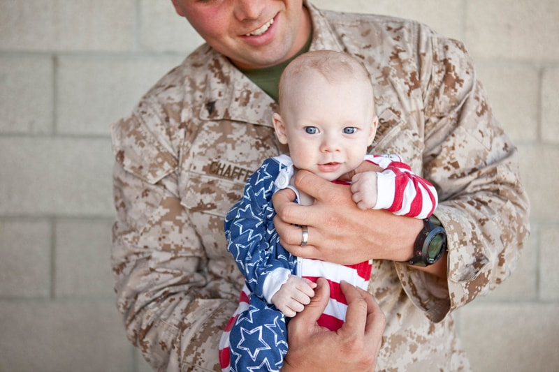 San Diego Military Homecoming, father holding little baby boy in an american flag outfit